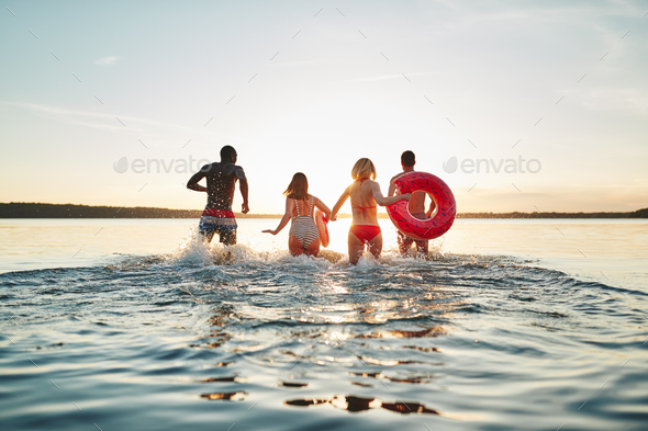 Friends making waves while running into a lake at sunset - Stock Photo - Images