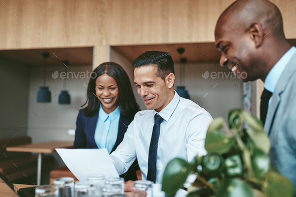 Three diverse businesspeople laughing while going over documents together - Stock Photo - Images
