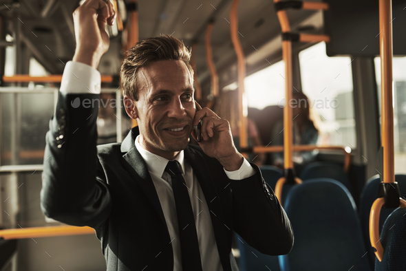 Young businessman talking on his cellphone during his morning commute - Stock Photo - Images