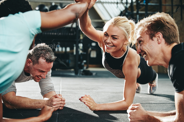 Female friends high fiving while planking at the gym - Stock Photo - Images