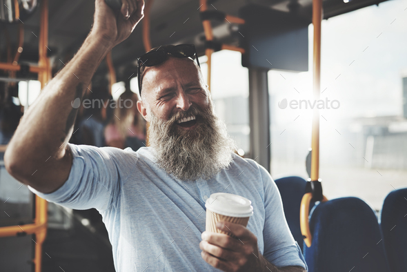 Bearded man standing on a bus drinking coffee and laughing - Stock Photo - Images