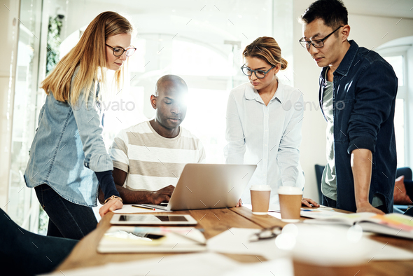 Diverse business colleagues working together around an office table - Stock Photo - Images