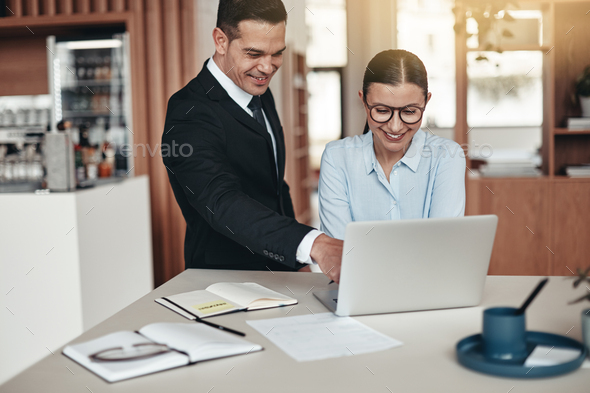 Two smiling office colleagues working together on a laptop - Stock Photo - Images