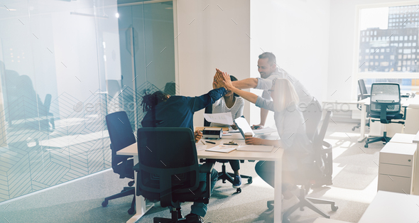 Smiling office workers high fiving together during a meeting - Stock Photo - Images