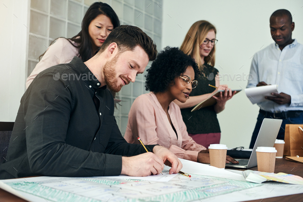 Smiling young architect at work with colleagues in an office - Stock Photo - Images