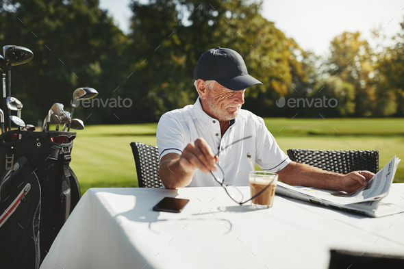 Senior man sitting at a cafe after playing golf - Stock Photo - Images