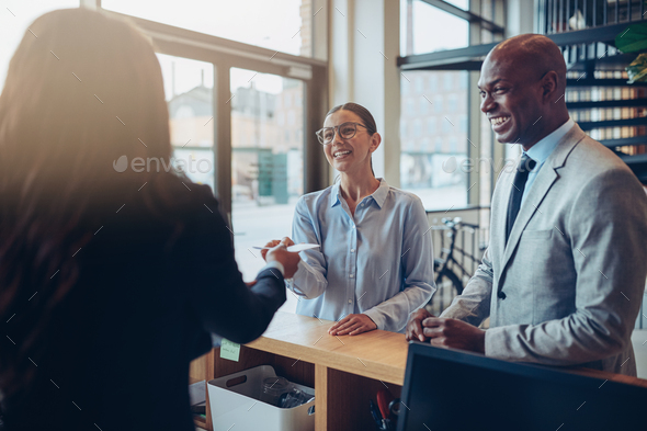 Two smiling hotels guests giving their reservation to reception - Stock Photo - Images