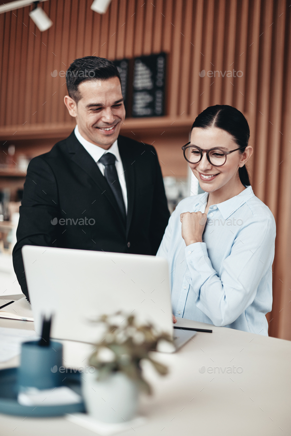 Two smiling businesspeople using a laptop together in an office - Stock Photo - Images