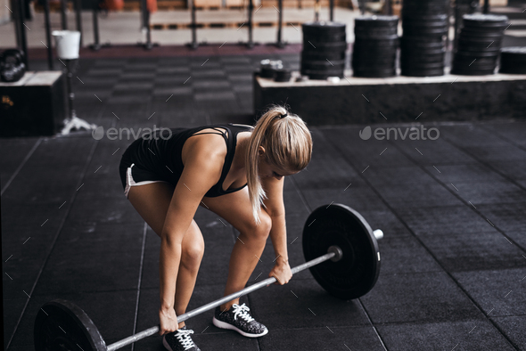 Young woman preparing to lift barbells in a gym - Stock Photo - Images