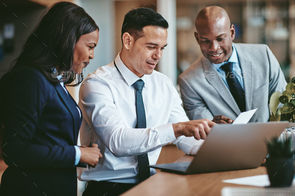 Diverse businesspeople smiling while working together at an office table - Stock Photo - Images