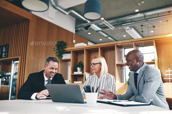 Three diverse businesspeople laughing while working together in an office - Stock Photo - Images