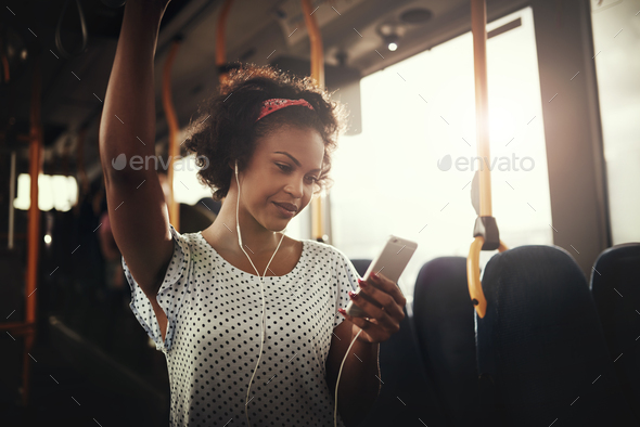Smiling young African woman listening to music on a bus - Stock Photo - Images