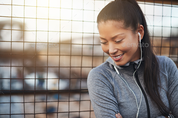 Asian woman smiling and listening to music before exercising outside - Stock Photo - Images