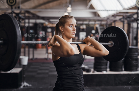 Young woman focused on lifting heavy weights in a gym - Stock Photo - Images