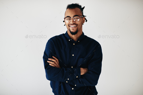 Confident young African American entrepreneur standing against a white background - Stock Photo - Images