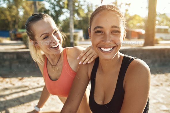 Two women laughing while taking a break from exercising outside - Stock Photo - Images