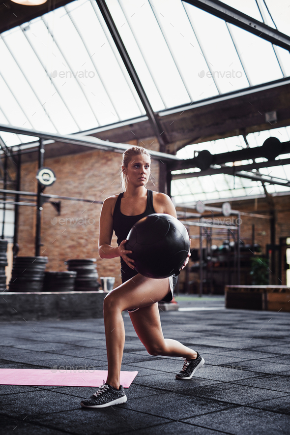 Fit woman working out with a ball at the gym - Stock Photo - Images
