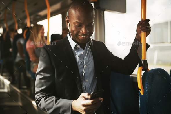 Smiling African businessman standing on a bus listening to music - Stock Photo - Images