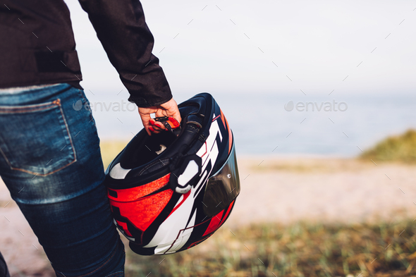 Woman holding a helmet on a motorbike offroad trip break - Stock Photo - Images