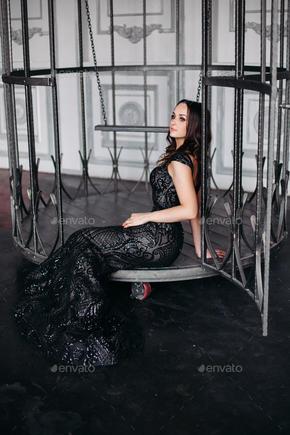 Beautiful brunette woman wearing shiny black dress posing in cage like bird - Stock Photo - Images