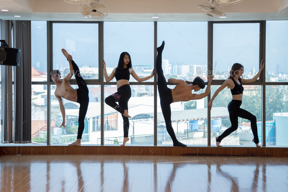 Asian dancers standing near window - Stock Photo - Images