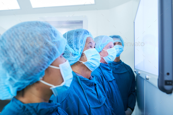 Surgeon team looking at screen - Stock Photo - Images