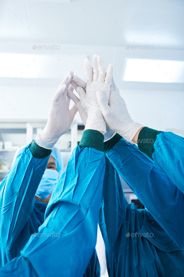 Unrecognizable surgeons high-fiving before surgery - Stock Photo - Images