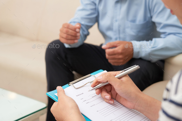 Doctor filling patient card - Stock Photo - Images