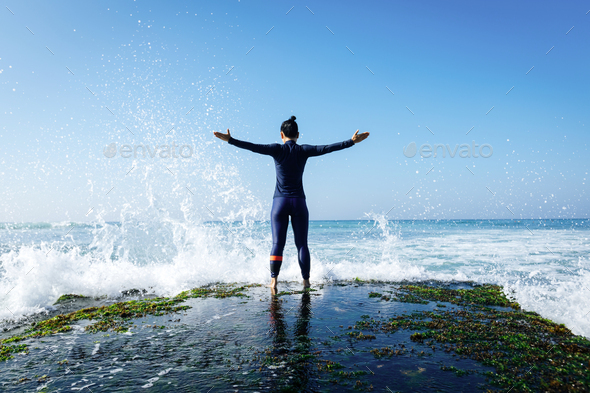 Strong woman open arms to the giant waves - Stock Photo - Images