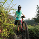 Woman mountain biker looking at the view on sunrise mountain top - PhotoDune Item for Sale