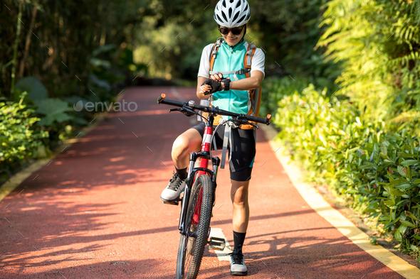 Woman biker set her smartwatch in park - Stock Photo - Images