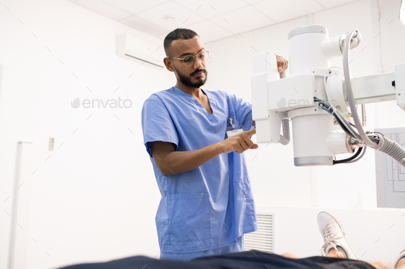 Bearded young mixed-race man in blue uniform using new medical equipment - Stock Photo - Images