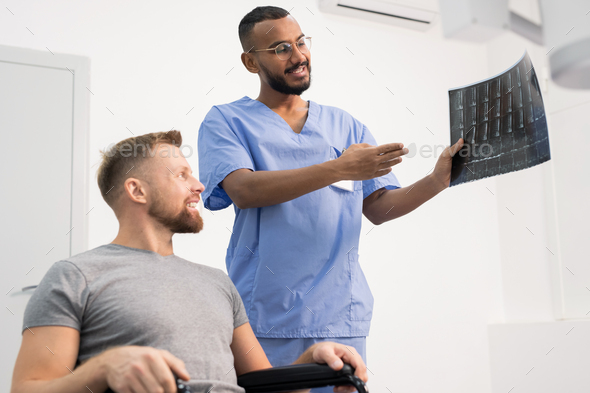 Radiologist in uniform showing patient on wheelchair x-ray of his broken joint - Stock Photo - Images