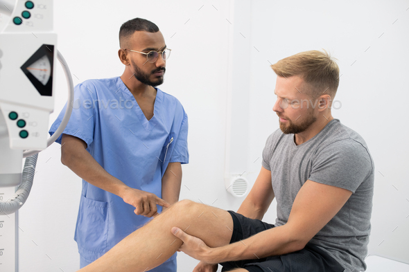 Young doctor in uniform consulting sportsman while pointing at his sick leg - Stock Photo - Images