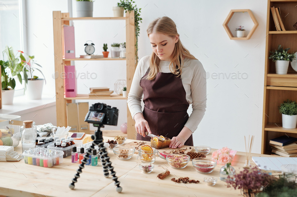 Young craftswoman shooting home master class of making handmade soap on camera - Stock Photo - Images