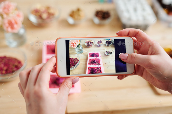 Hands of girl holding smartphone over table while taking photo of handmade soap - Stock Photo - Images