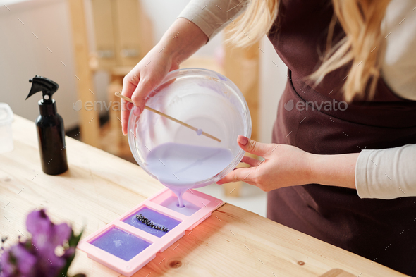Hands of craftswoman in apron pouring lilac liquid soap mass into silicone molds - Stock Photo - Images