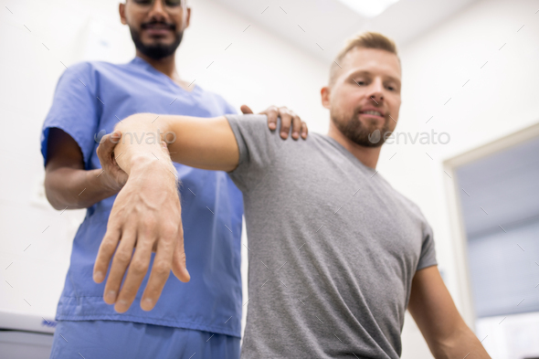 Masseur in blue uniform holding sick arm of patient while massaging it - Stock Photo - Images