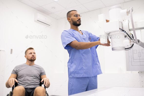 Young sportsman on wheelchair looking at doctor testing new medical equipment - Stock Photo - Images