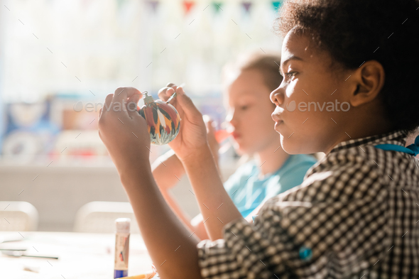 Cute African schoolboy holding handmade decorative Christmas toy ball - Stock Photo - Images