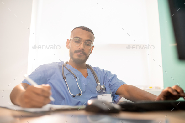 Bearded serious doctor or intern in uniform making working notes by table - Stock Photo - Images