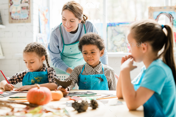 Multicultural schoolkids in aprons sharing their ideas of handmade decorations - Stock Photo - Images