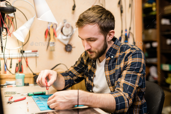 Repairman bending over broken gadget and using screwdriver to fix tiny parts - Stock Photo - Images