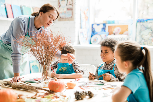 Young teacher putting handmade paper bat on dry branch in the center of table - Stock Photo - Images