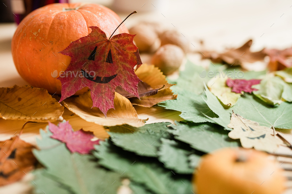 Dry colorful autumn foliage, big ripe pumpkin and drawn faces on leaves - Stock Photo - Images