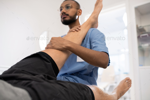 Qualified medical professional massaging sick knee of patient in hospital - Stock Photo - Images