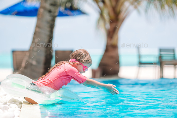 Little active adorable girl in outdoor swimming pool ready to swim - Stock Photo - Images