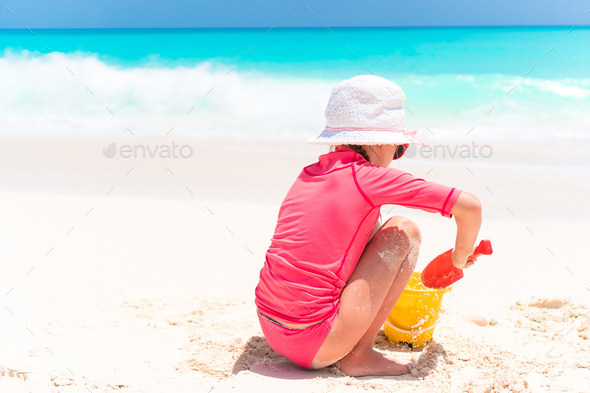 Adorable little girl playing with beach toys during tropical vacation - Stock Photo - Images