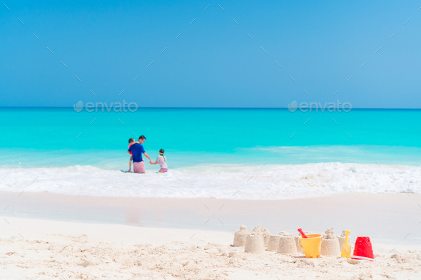 Sandcastle at white beach with plastic kids toys - Stock Photo - Images
