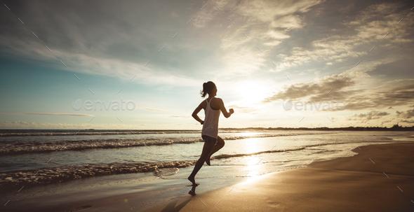 Woman running on sunset beach - Stock Photo - Images